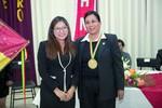 Yesenia Yarhui entrega la medalla de reconocimiento a la directora Gladys Paredes.