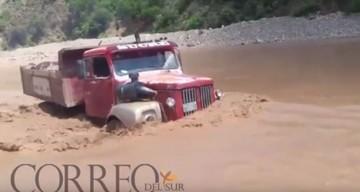 Chofer desafía al río y logra cruzar con una volqueta llena de piedras