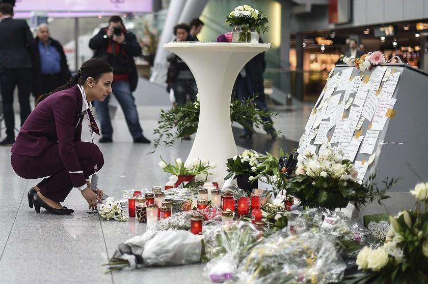 Una empleada de Germanwings depsita flores en memoria de las víctimas del vuelo 4U 9525 de Germanwings. Foto: EFE