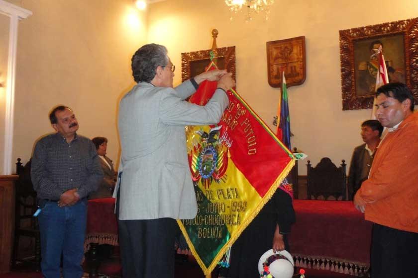 Germán Gutiérrez impone la condecoración Juana Azurduy de Padilla al estandarte del colegio.