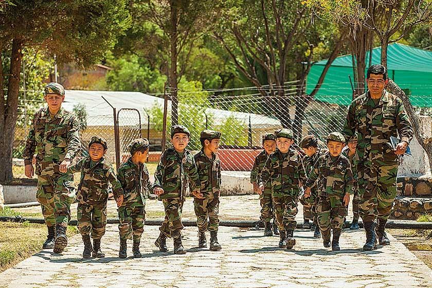 Un grupo de niños del kinder Teniente Edmundo Andrade, acompañados por un instructor (derecha) y un cadete.