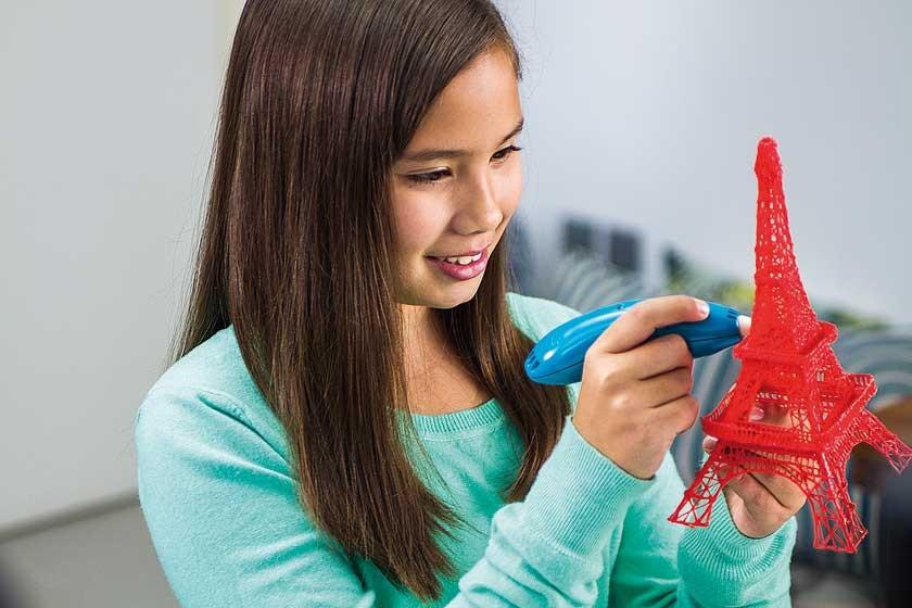 En la imagen, una niña haciendo una réplica de la torre Eiffel con el bolígrafo en 3D.
