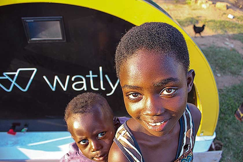 Unos niños ante la máquina Wtly 2.0 instalada en Ghana.