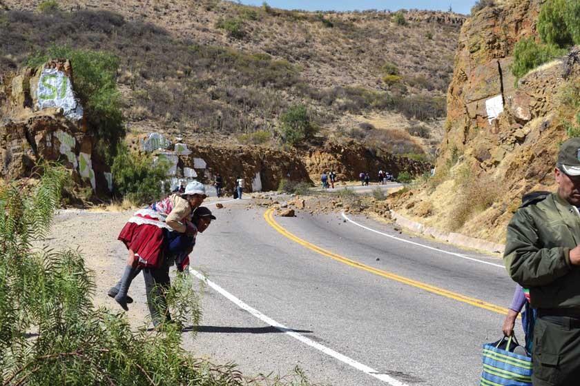 A PIE. Una anciana inválida es cargada por su hijo debido al bloqueo de la vía.