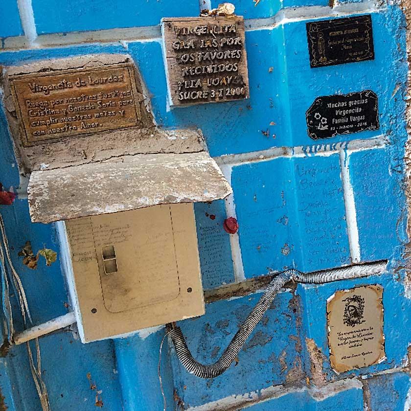 Diferentes placas evocativas y humildes agradecimientos escritos a mano sobre una de las paredes del santuario.