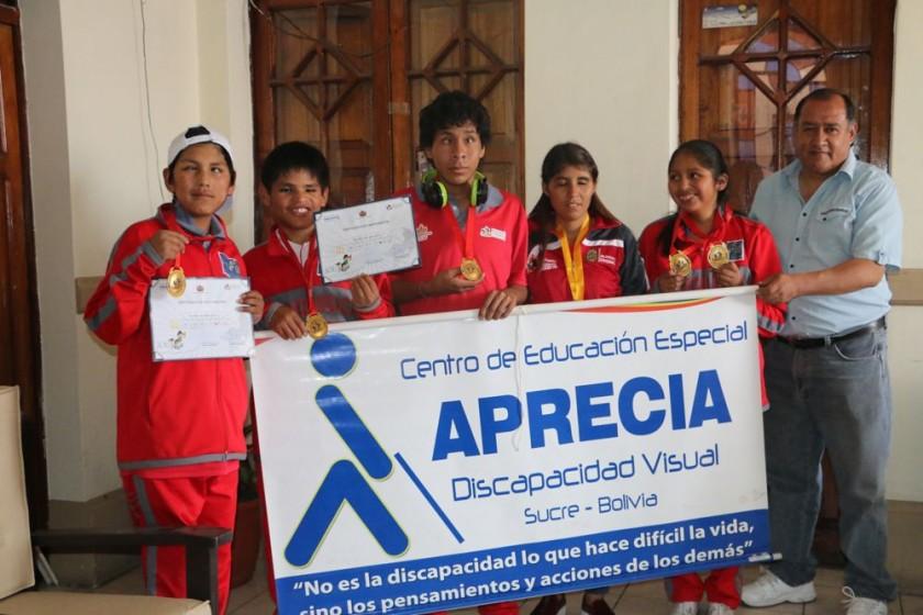 Los ganadores de oro lucieron sus medallas junto a su entrenador.