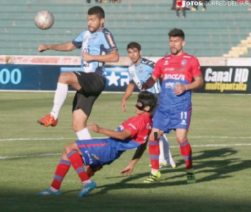 defensor de Blooming rechaza el balón cuando Edzon Pérez intentaba controlarlo.