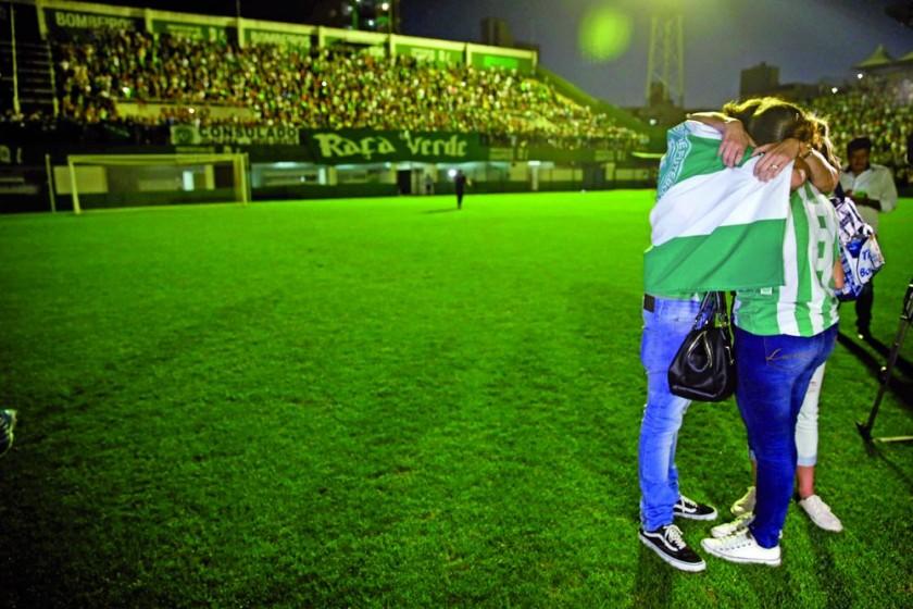 Familiares de jugadores y directivos del Chapecoense saludan a los aficionados durante la vigilia en la Arena Condá...