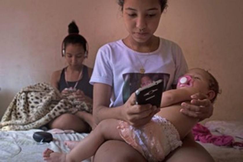Nayane, de 15 años, sostiene en brazos a su hija Ana Sophia, de 10 meses, mientras manda mensajes con el celular.