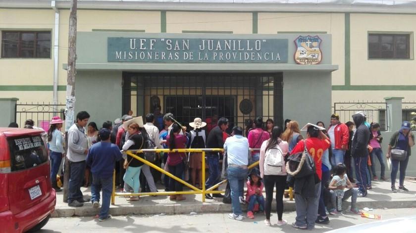 Decenas de padres de familia forman filas en la unidad educativa San Juanillo. Foto: Enrique Quintanilla