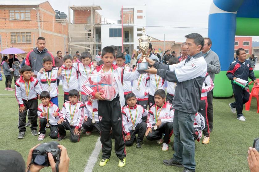 El capitán de Atlético Nueva Era recibe el trofeo de la categoría Sub 11 del Campeonato de Verano de Fútbol