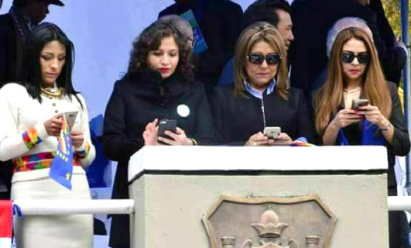 Las ministras miran sus celulares mientras se desarrolla el desfile. Foto: Facebook