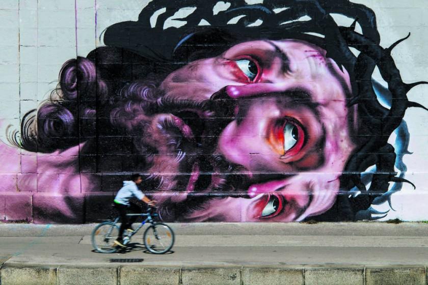 Viena (Austria), 31/08/2016.- Un hombre pasea con su bicicleta junto a una pintada de Jesucristo en Viena, Austria.