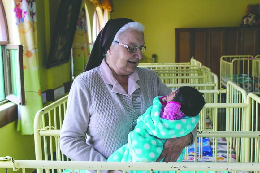 La hermana Clementina recibe donaciones de una familia.