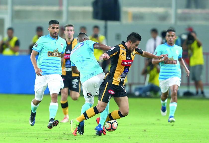 El delantero atigrado Rodrigo Ramallo es derribado por un defensor peruano