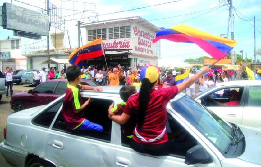 MANIFESTACIÓN. Un grupo de personas ondean banderas venezolanas durante el plebiscito opositor en la ciudad de Maracaibo