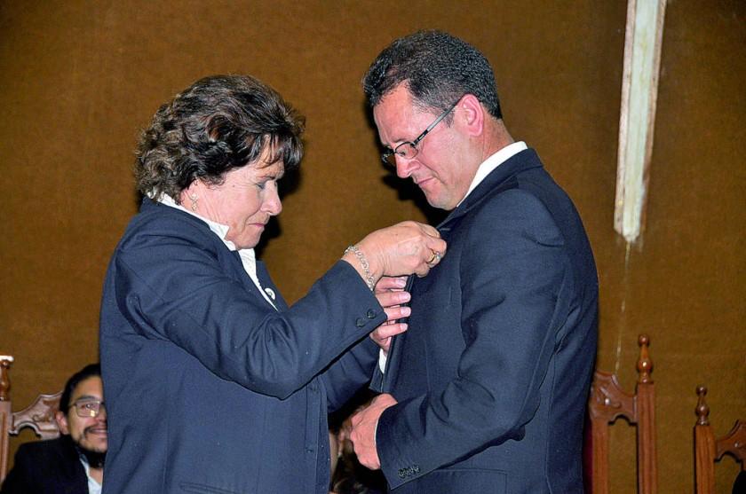El director General, Lic. Wilmer Pérez, recibe un reconocimiento de Rose Marie Lora de Martínez.