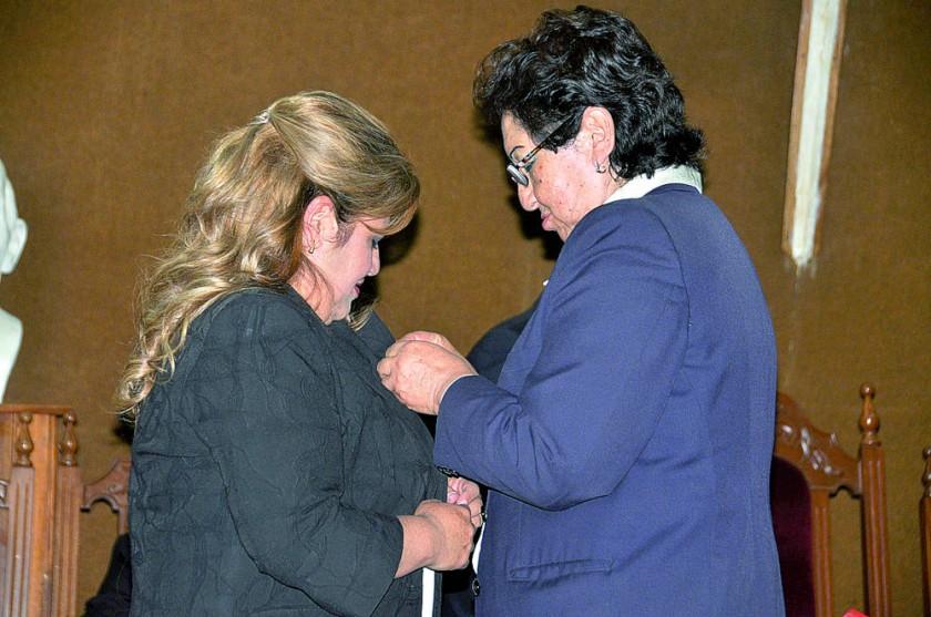 Virginia Urquidi de Torres entrega un reconocimiento a Riosed Paredes.