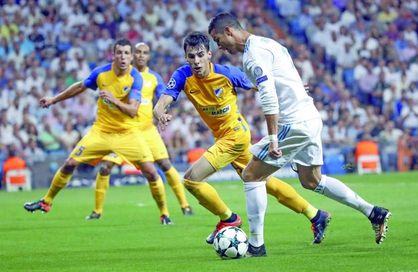 Cristiano Ronaldo (d) es marcado por tres jugadores del Apoel Nicosia en el partido de ayer, en Madrid.
