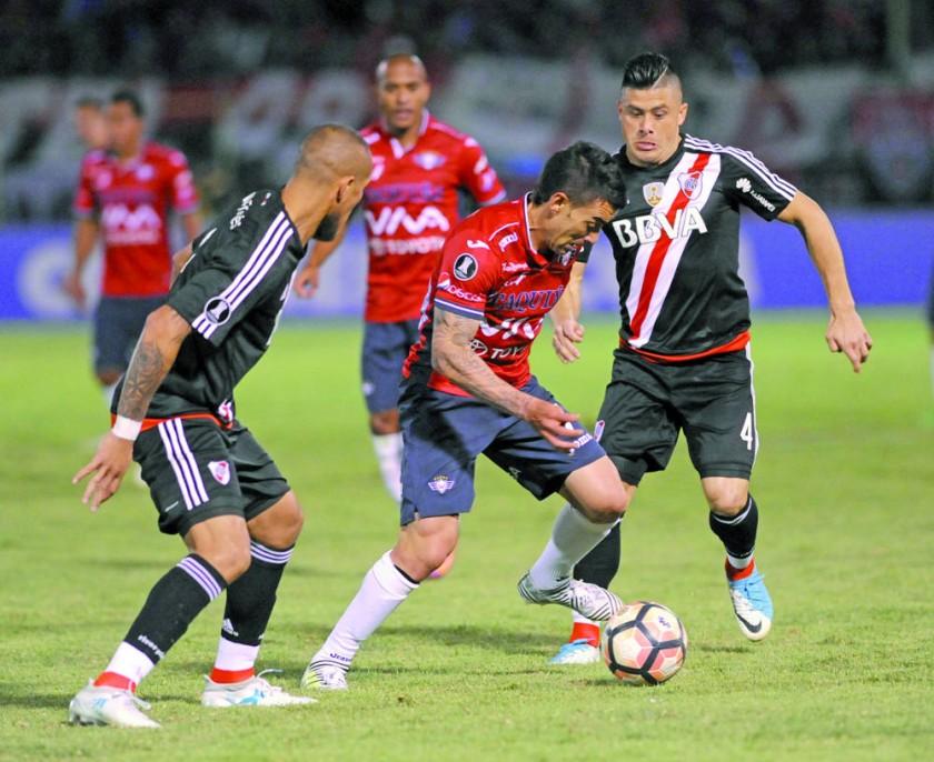 Marcelo Bergese controla el balón ante el asedio de jugadores millonarios.