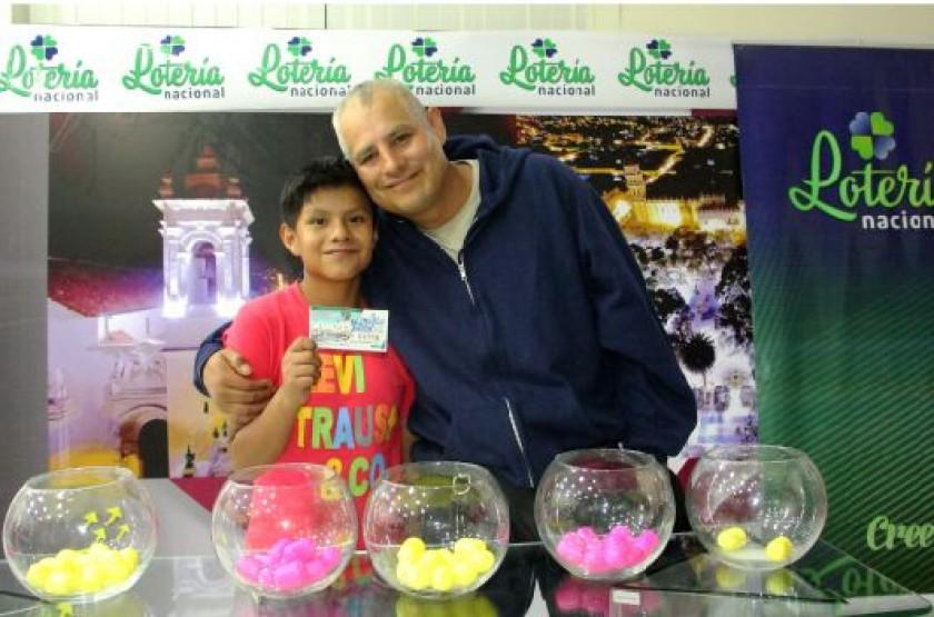 GANADORES. Antonio Reyes y su hijo Manuel Rolando Segarra muestran su billete.