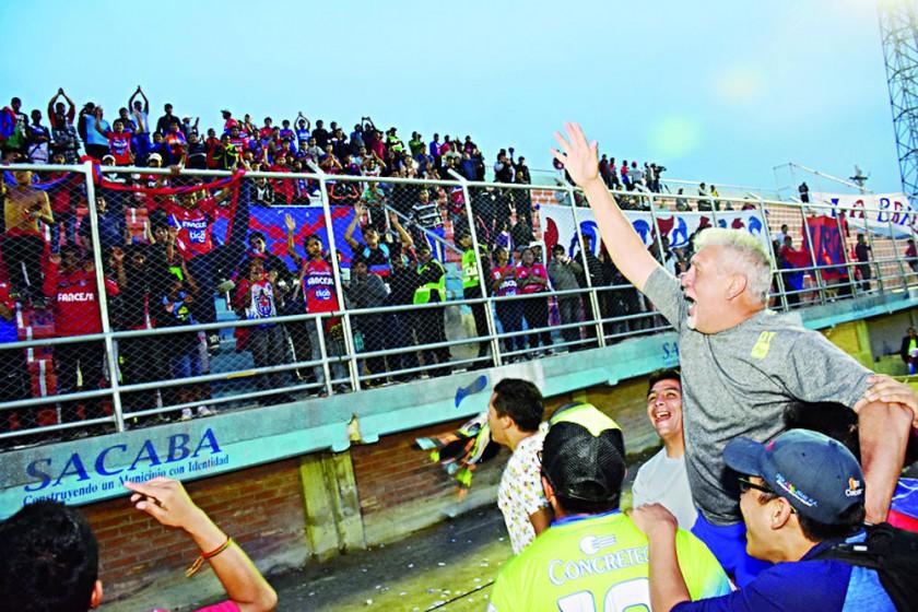 El entrenador Oscar Sanz saluda a los hinchas estudiantiles.