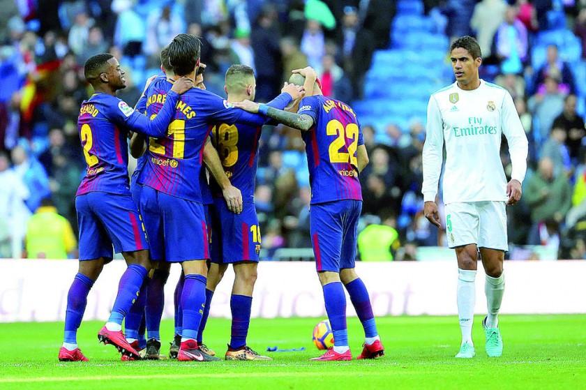 El festejo de los jugadores del Barcelona ante la desazón del defensor madridista Raphael Varane (d).