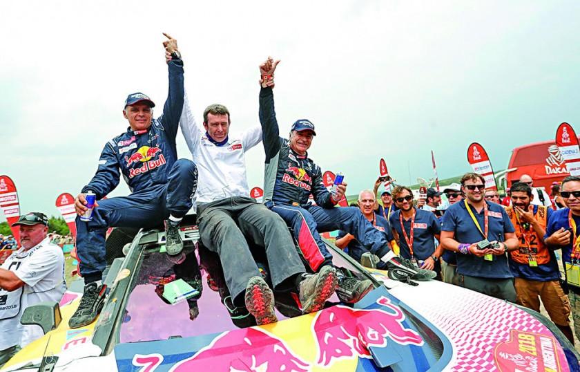 El español Carlos Sainz celebra con su copiloto y compatriota Lucas Cruz y Bruno Famine, manager del equipo...