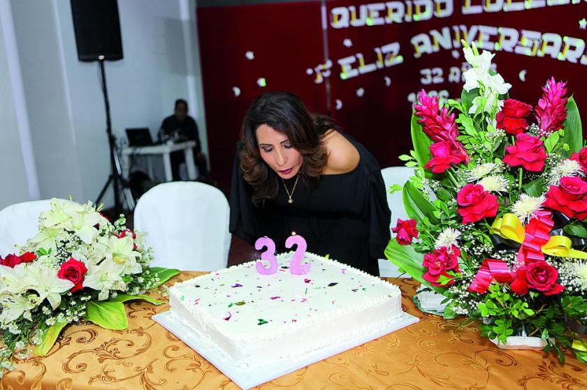 La directora Sandra Cabrera apaga la vela de la torta del colegio.