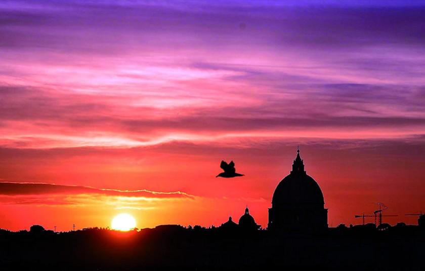 El sol se esconde en el horizonte tras la Basílica de San Pedro, en el Vaticano, donde se dice que está enterrado el...