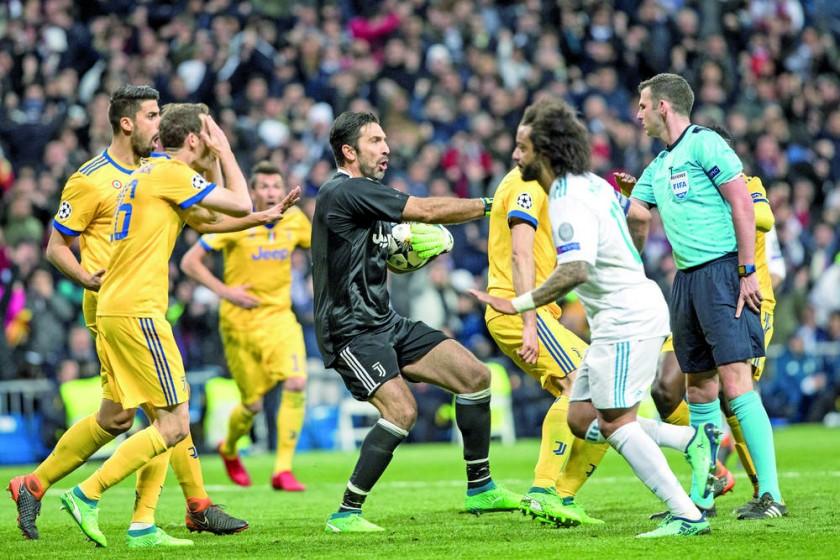 El inglés Michael Oliver (d) recibe críticas de los jugadores de Juventus tras cobrar un penal que los dejó fuera.