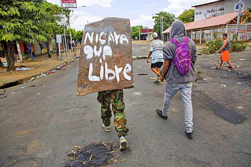DISTURBIOS. Una joven camina con un escudo sobre su espalda durante las protestas en Managua.