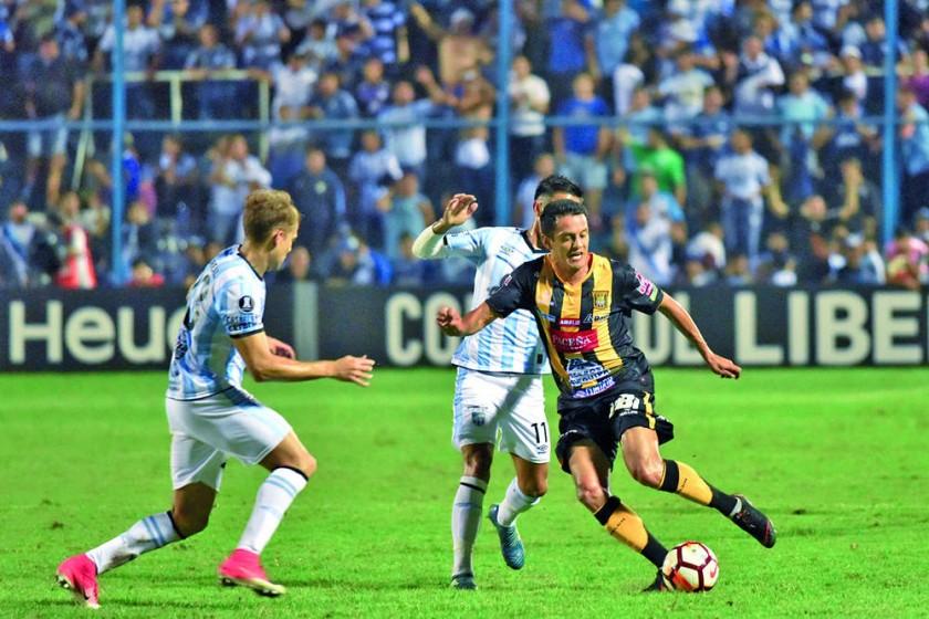 El volante atigrado Jhasmani Campos (d) intenta evadir la marca de dos jugadores de Atlético Tucumán ayer, en Argentina.