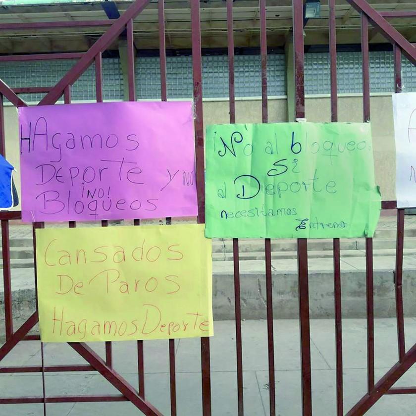 Los carteles pegados en la puerta del complejo de raquetbol.