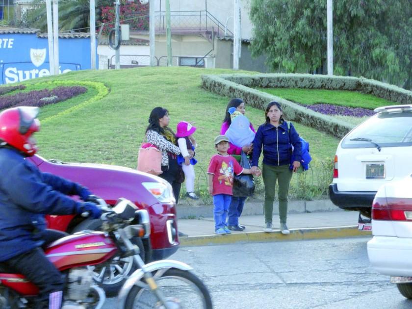 RIESGO. Una familia espera para cruzar la avenida Juana Azurduy de Padilla en medio del intenso tráfico de motorizados.