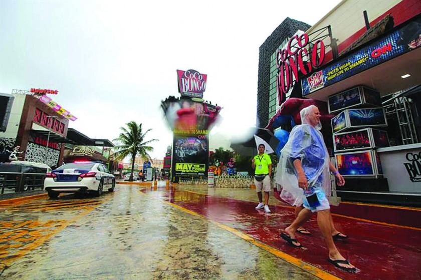 EMERGENCIA. Turistas se protegen de la lluvia en el balneario de Cancún.