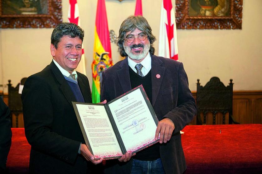 El alcalde Iván Arciénega hace la entrega del reconocimiento al sacerdote Bernardo Gantier.