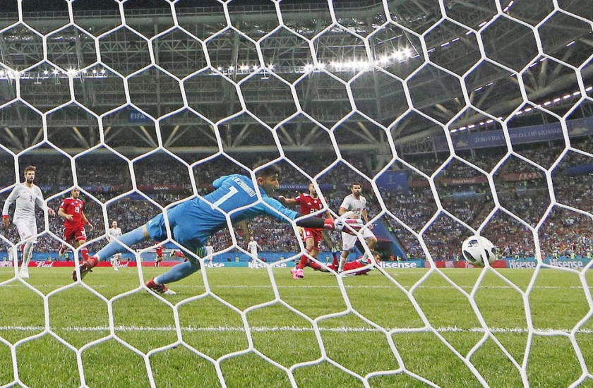 El delantero español Diego Costa toca el balón ante la arremetida del iraní Morteza Pouraliganji