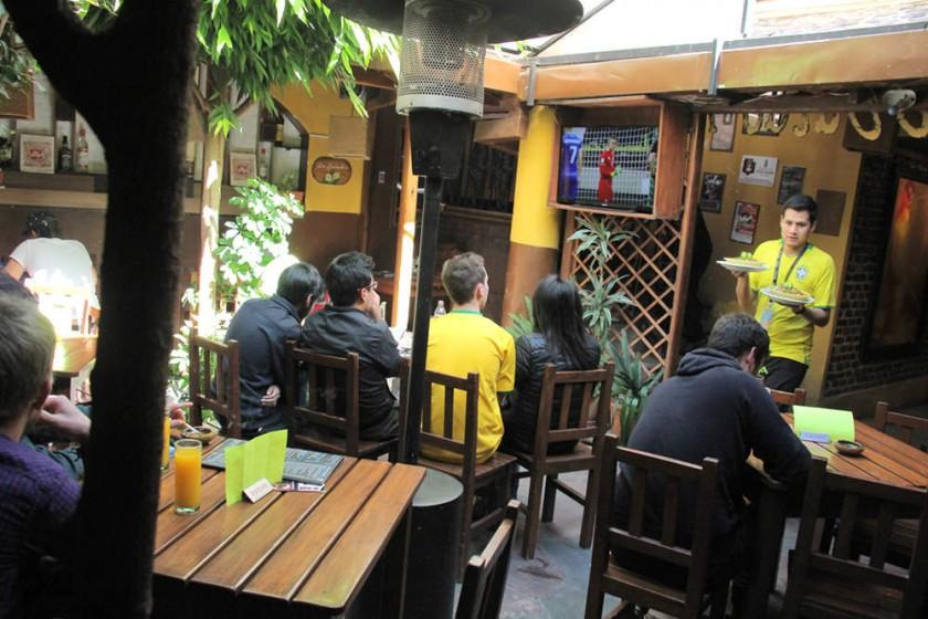 Espectadores nacionales y extranjeros observan el partido Brasil-México en instalaciones del Joy Ride. capitales