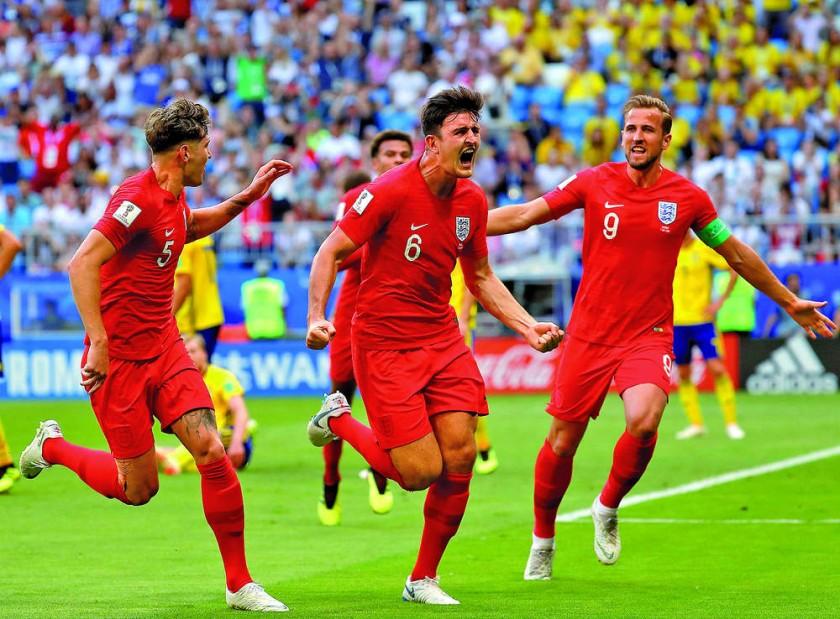 John Stones (i), Harry Maguire (c) y Harry Kane gritan el primer gol de Inglaterra en la victoria ante Suecia