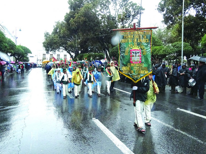 DESFILE. La unidad educativa Agustín Iturricha a su paso por la plaza 25 de Mayo, en plena lluvia, ayer.