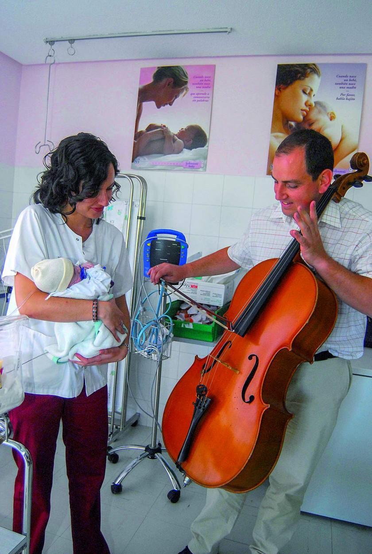 Violonchelista en una intervención de terapia con música en la sección de neonatología de un hospital, mientras...