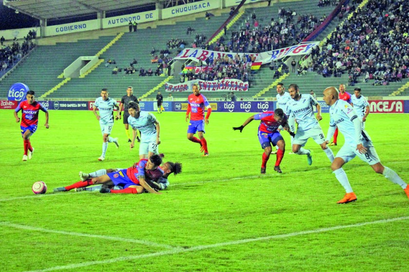 El delantero estudiantil Oscar Díaz y el defensor académico Leonel Morales cayeron al piso después de pelear por la...