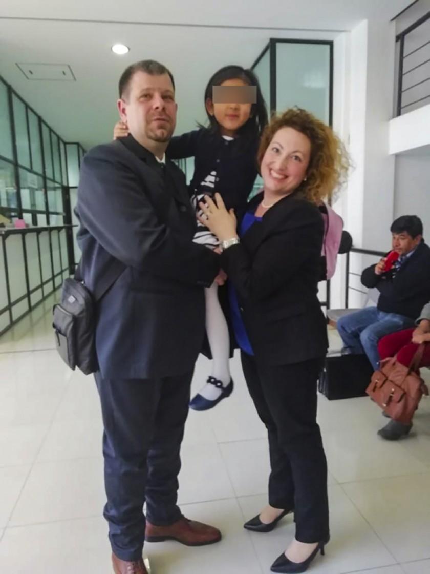 Una niña con sus padres adoptivos italianos.