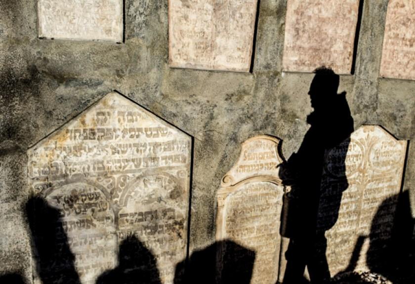 La sombra de un hombre se proyecta entre nichos en el cementerio del barrio judío de Praga (República Checa). Este campo