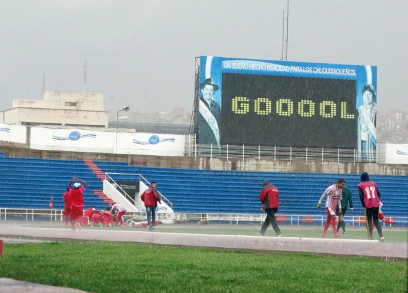 El festejo de los jugadores albirrojos en medio de la torrencial lluvia caída ayer en Sucre. El tablero reflejó el grito