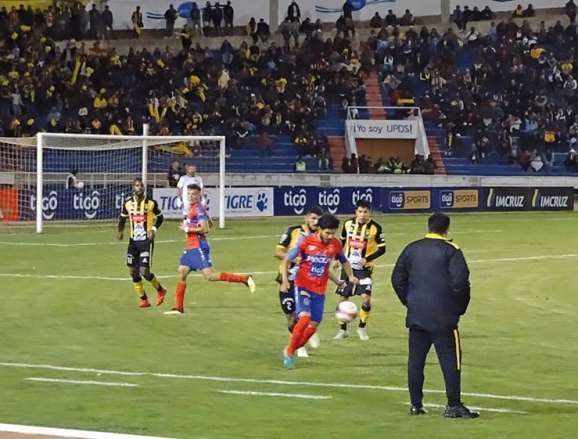 El volante estudiantil Adriel Fernández (c) domina el balón ante la marca de dos jugadores atigrados y la atenta mirada