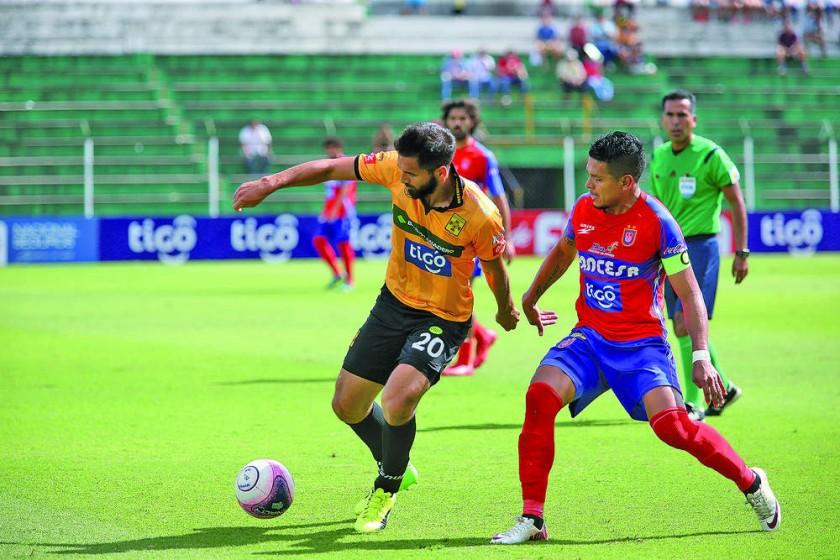 El capitán de Universitario, Marcos Andia (d), intenta robarle el balón al delantero canario Carlos Schmidt, en el parti