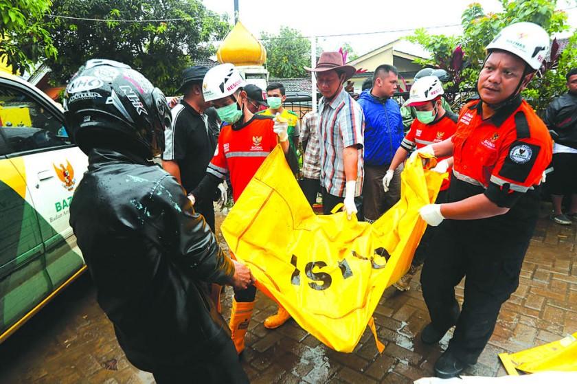 LUTO. El equipo de rescate evacúa el cuerpo de una víctima después de que un tsunami golpeó el estrecho de Sunda en Pand