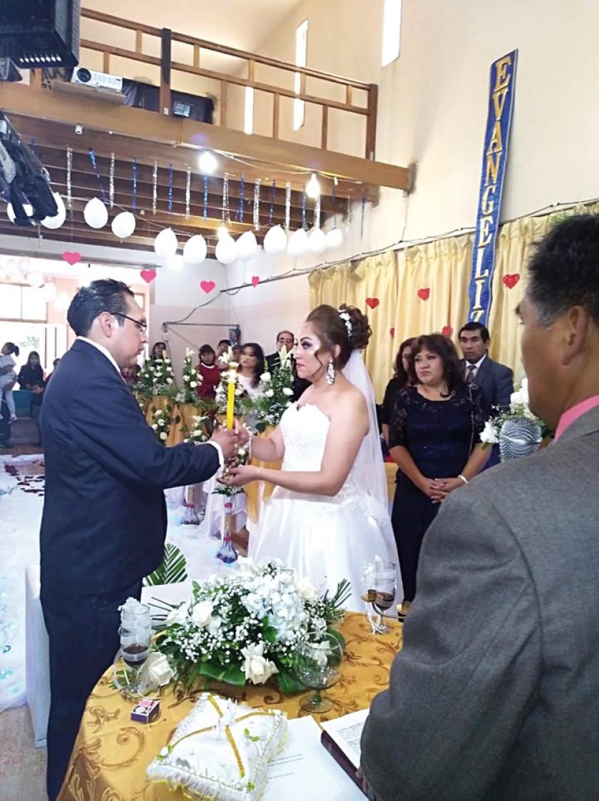 Freddy Christian Ayaviri Delgadillo y Paola Patricia Serrano Barriga en el momento del encendido de la vela amarilla que